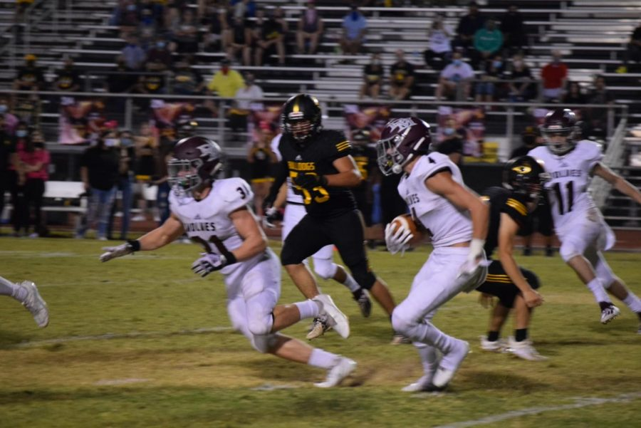 "A 'DIFFERENT' VIBE: During a 49-21 victory against Barry Goldwater, senior tight end Anthony Pescatore (31) blocks for the kick returner. ""The vibe is going to be totally different since there is no Wolfden--that huge support system is gone,"" Pescatore said. The Wolves leaped to a fast 3-0 start, outscoring opponents 97-38--but the team was forced to postpone its Homecoming game Oct. 23 against Casa Grande after a player from Barry Goldwater tested positive for coronavirus."