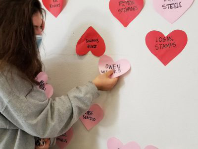 STEALING HEARTS Katie Hofmann (10) grabs freshman Owen Weeks heart Friday morning, one of more than 1,600 hearts hung by Student Council the night before.
